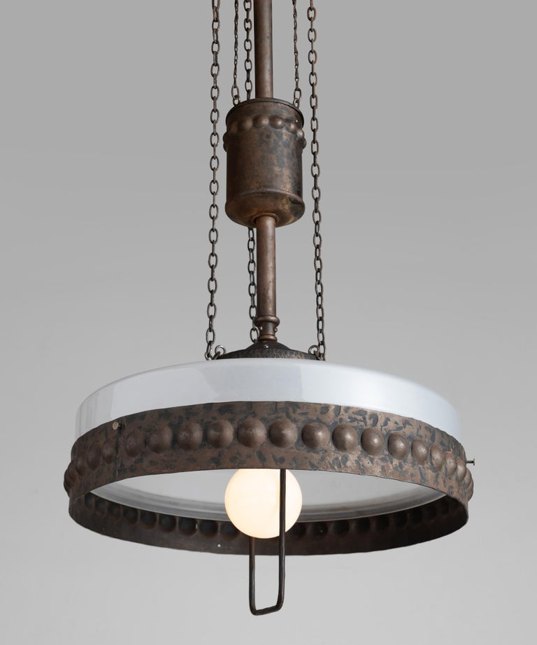 Ornate iron fixture with frosted glass shade.