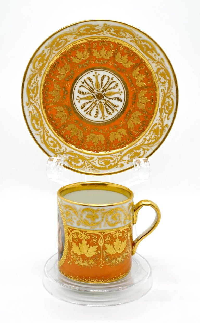 The cylindrical white cup is painted two-thirds dark yellow from the bottom upwards, and over the entire cup there is ample gold decoration with vine leaves and tendrils, gold also on the top edge and the upper inner rim. Opposite the curved handle