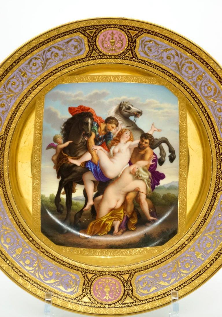 Exceptionally decorated porcelain plate: in the mirror, large, upright rectangular panel with beveled corners, framed by a gold-impasto palmette ribbon painted on matt gold, in front of a glossy gold background, image of the 'Abduction of Phoeba