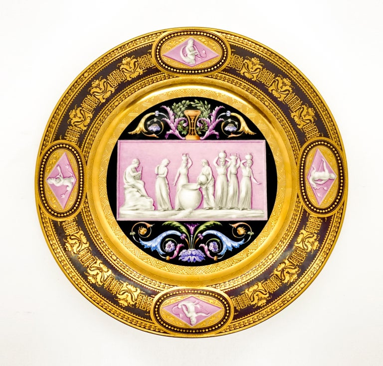 Extraordinarily decorated porcelain plate: in the mirror a pink, transversely rectangular picture panel against a black background, framed by brightly colored leaf and feather tendrils in the segments on the long sides, a cup 