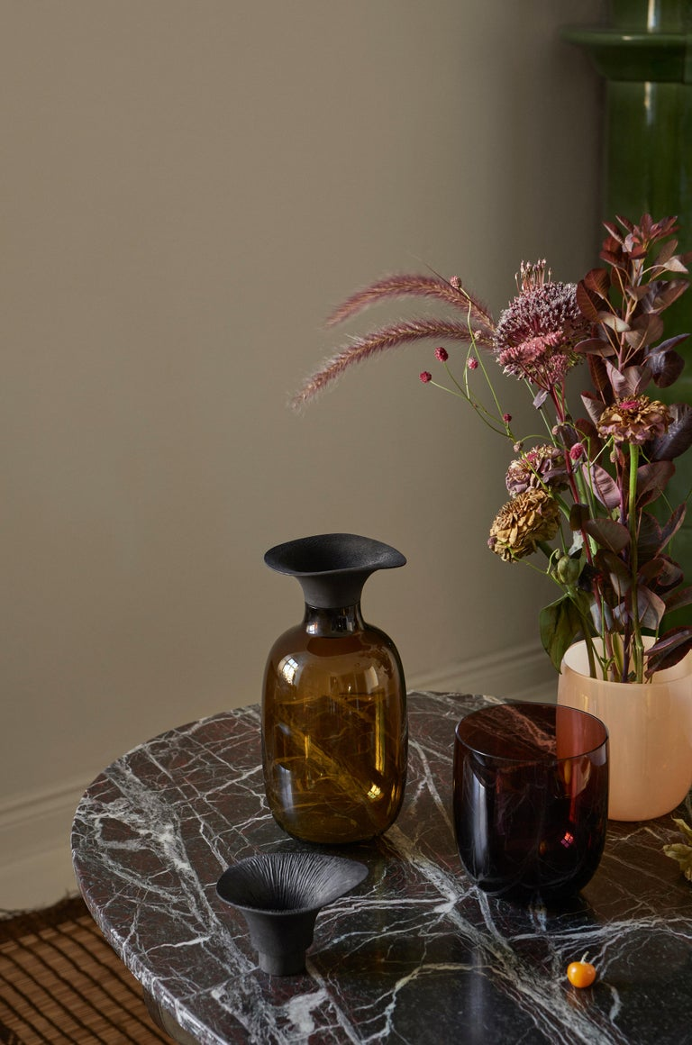 Combining hard glass with warm wood, the Vieno bottle is designed to combine harmoniously with floral arrangements. Vieno is like smooth, calm water: it gives life to flowers and branches that are given to it, letting them reach out towards new