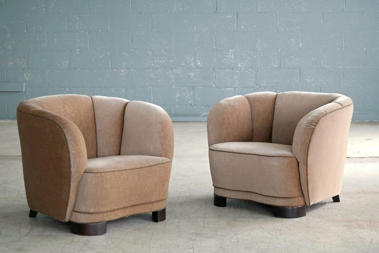 Incredibly comfortable, exuberant, and superbly made pair of Danish lounge chairs perfectly capturing the essence of 1940s Danish design coming out of the Art Deco era and into the midcentury. The curved backrests and low slung proportions and block