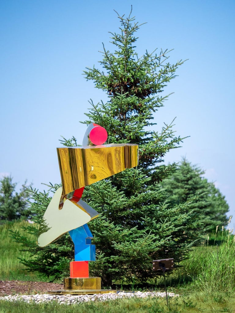 A column of colorful and precariously stacked shapes glitters in the sun. This playful outdoor sculpture by Viktor Mitic may also be installed indoors.  Serbian-born Viktor Mitic earned a BFA from the University of Toronto in 1995 with studies in
