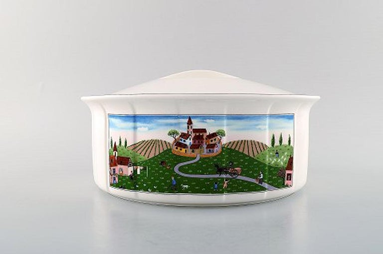 Villeroy & Boch Naif dinner service in porcelain. Oval lidded tureen decorated with naivist village motif. In very good condition. Stamped. Measures: 25 x 11.5 cm. Designed by Gérard Laplau. Motives of families, villages and biblical scenes in