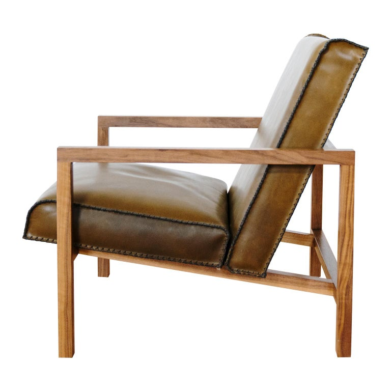 The Vincent lounge chair features a heritage leather seat and back and finely crafted black walnut wooden frame.  Displayed here in olive green leather, the Vincent is a true statement piece, sure to be noticed and make a Stand out impression in