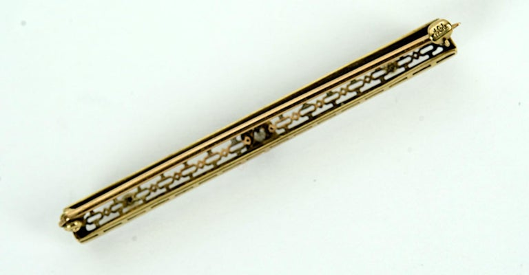 Vintage 10 Karat Yellow Gold, Diamond and Seed Pearl Bar Pin or Brooch. Early 20th c with a central 2.5mm full cut diamond set in a floral mount and a pair of 2mm seed pearls in a beautifully detailed, pierced and decorated frame, hallmarked 10K.