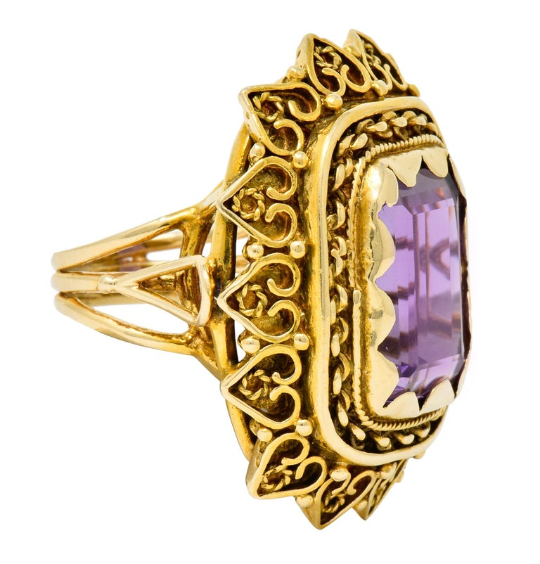 Centering an emerald cut amethyst weighing approximately 13.64 carats, transparent and a medium-light purple color  Set in place by scalloped polished gold and surrounded by twisted rope and chain link motifs  With radiating petal-like surround