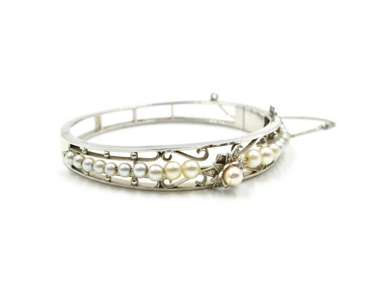 Designer: custom design Material: 14k white gold Pearls: round 3.40mm-4.40mm cultured pearls Dimensions: bracelet will fit up to 6-inch wrist and is 3/8-inch wide, with 3-inch safety chain Weight: 17.08 grams