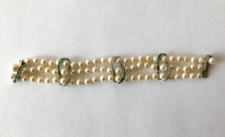 Vintage three strand pearl bracelet with 14k white gold accents containing channel set emeralds and diamonds.  Emeralds do have natural inclusions and perhaps a small chip or two. These are very hard to see with the naked eye and mostly only under