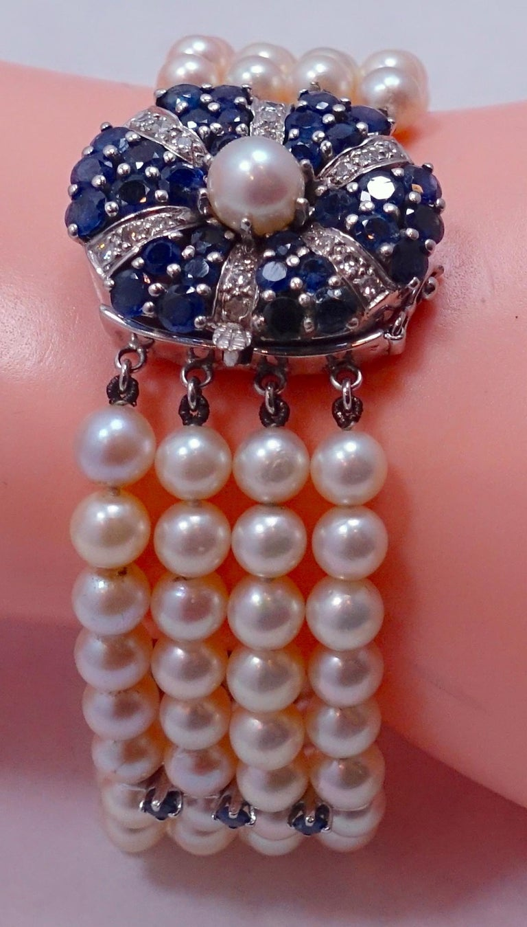"""This vintage pearl bracelet has an extremely elegant centerpiece. It has a sophisticated floral design with diamonds and sapphires with a pearl center … in a 14kt white gold setting.  This bracelet measures 7-1/2"""" long and the centerpiece is 1"""" in"""