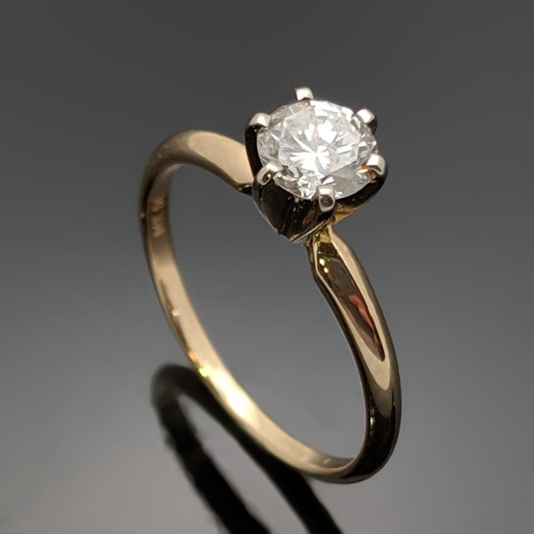 This Vintage  14kt yellow gold ring is a timeless style with a round brilliant cut diamond at an estimated weight of 0.51ct and knife's edge band. Estimated weight of gold is 1 gr.   We will size it for you.