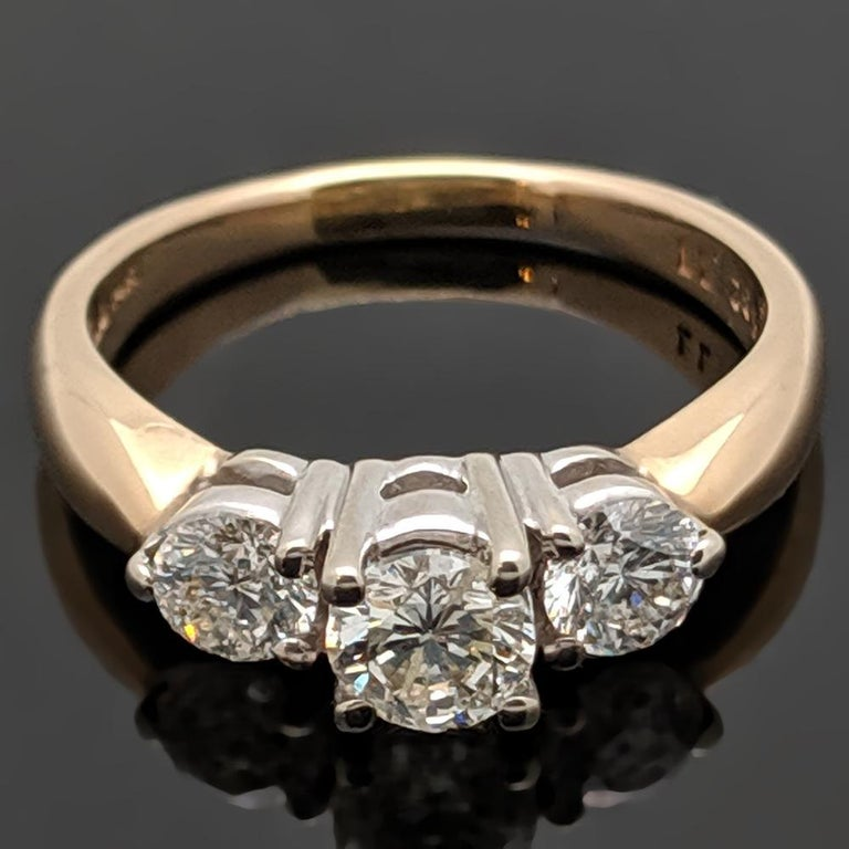 A vintage three-stone 14kt yellow gold ring featuring a center round brilliant cut diamond with an estimated weight of 0.31ct and side diamonds at an estimated 0.50 cttw. Estimated weight of gold is 2 gr.   We will size it for you.