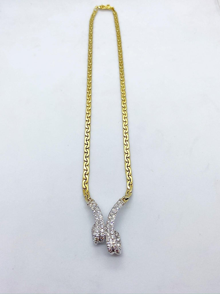 This 14 karat gold necklace is designed with a white gold center ribbon like section set with round Brilliant Diamonds. The yellow gold chain is a flat c link. The total length of the necklace measures 15.5