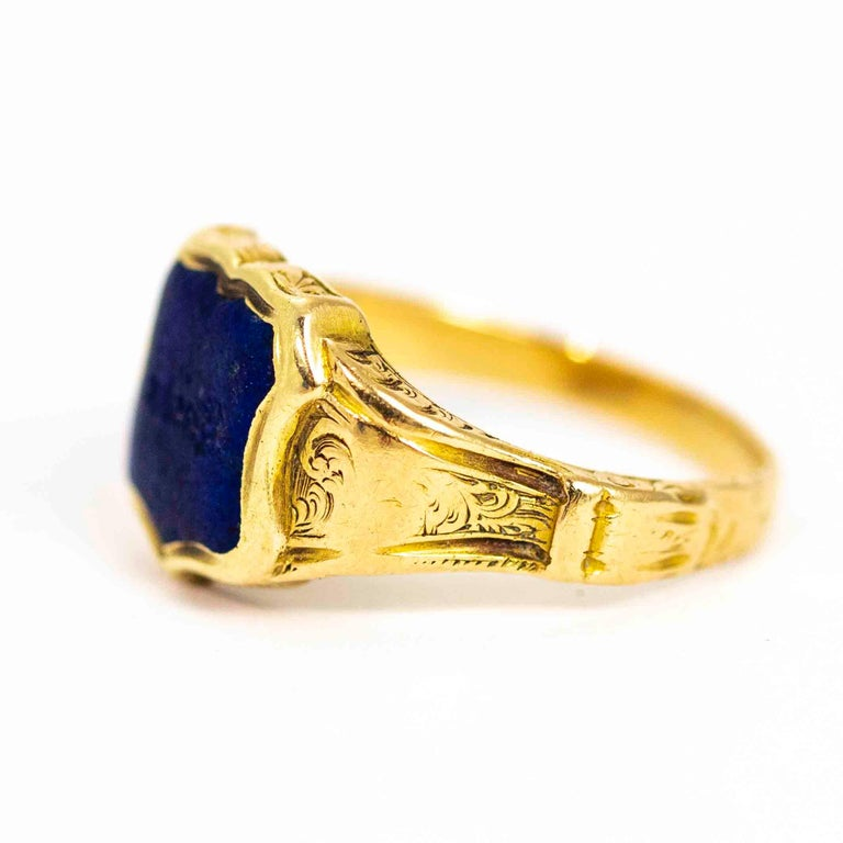 A fine vintage signet ring set with a wonderful shield cut lapis lazuli. This stone sits between beautiful hand-chased shoulders. The lapis is engraved with a latin phraise. Modelled in 18 carat yellow gold.  Ring Size: UK M 1/2, US 6 3/4  Front