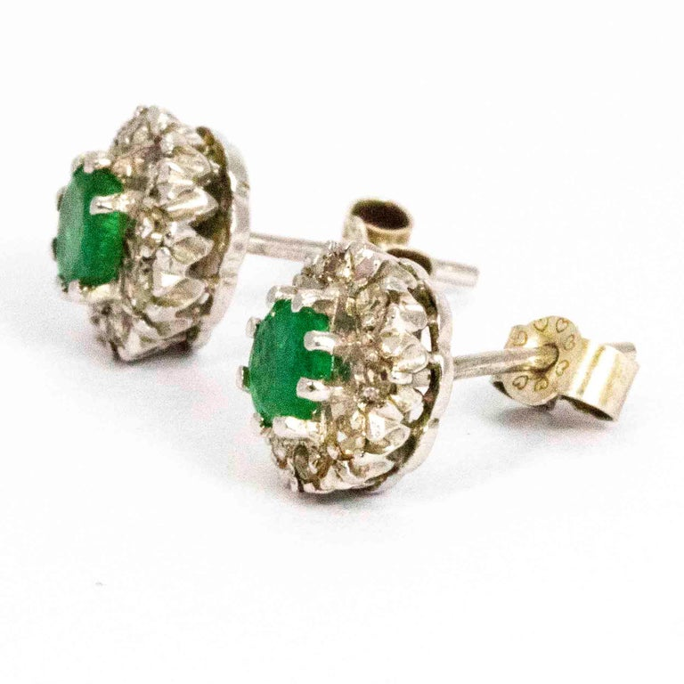 A superb pair of vintage cluster earrings centrally set with beautiful round emeralds surrounded by stunning diamond halos. Modelled in 18 carat white gold with butterfly stud backs.  Cluster Width: 9mm