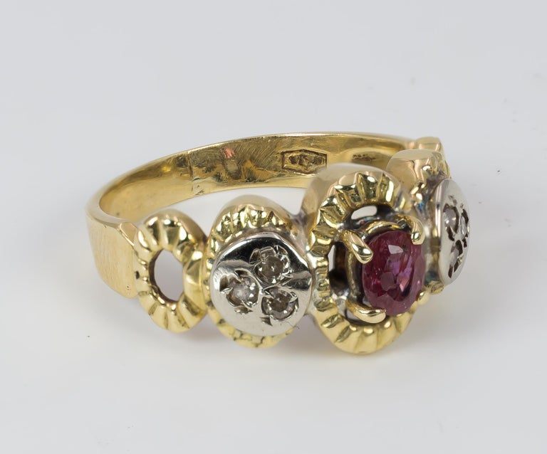 This beautiful vintage ring, dating from the 1970s, is set with a central ruby, flanked on either side by three rose cut diamonds. The ring is crafted in 18K gold throughout, and has a beautiful openwork to the shoulders.   MATERIALS 18K gold, ruby