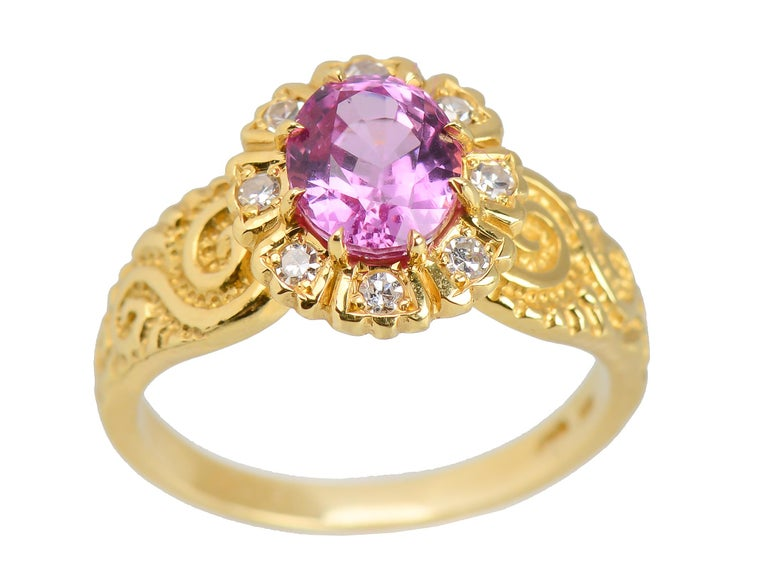 In shadow or sunlight, this is the most vivid of pink sapphires, weighing approximately 1.7 cts of sizzling pink peony shades. Surrounding the vivacious pink, a halo of eight single cut diamonds of approx..16 cts, G-H color and VS clarity, is a