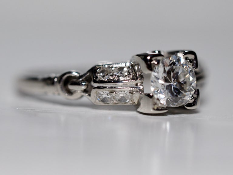 18 karat white gold vintage ring featuring a round brilliant cut Diamond set in four prongs measuring  4.71 - 4.71 x 2.87 mm and weighing approximately .38 carats,  SI clarity  H - I color.   Accented by 8 single cut diamonds weighing approximately