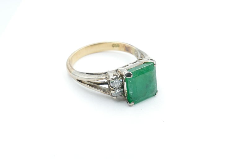 The good Emerald Stone featured in this very attractive Vintage Ring is 2.74 carats in weight, Bluish-green Colour, medium Tone, 4 claw set and is flanked by 4 Round Brilliant cut Diamonds, Colour G/H & Clarity SI1-SI2, individually claw set. The