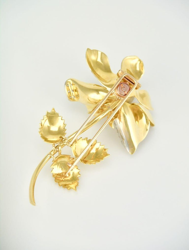 A beautifully realised pin in the form of a realistic rose shape with open petals with the tips decorated in diamonds. The yellow gold is textured with a brushed finish to the flower and leaves, and then contrasted with a polished finish to the stem