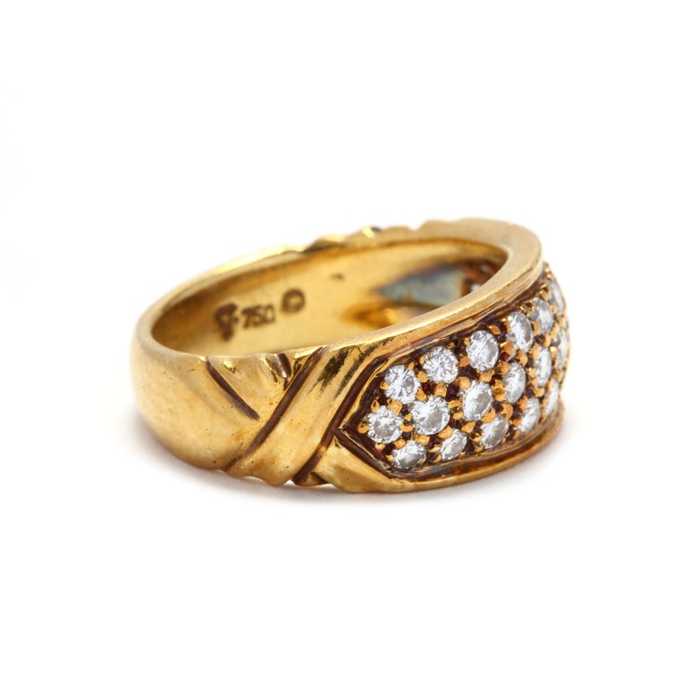 Vintage 18 karat yellow gold and diamond band. A slightly tapered band with three rows of pavé set, full cut round diamonds weighing approximately .81 total carat and with a crisscross motif on the shank.  Stones: - diamonds, 31 stones - full cut