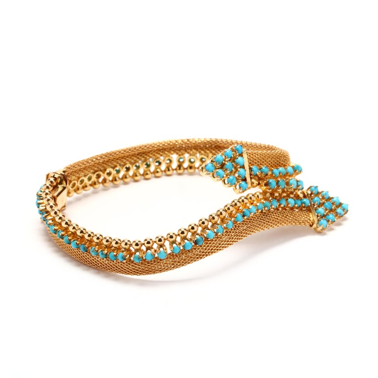 Circa 1960, 18 karat yellow gold turquoise bracelet. In a bypass design, they bracelet features a mesh link with round cabochon turquoise and beaded detailing and terminating at two points with turquoise detailing.  Stones: -turquoise - round