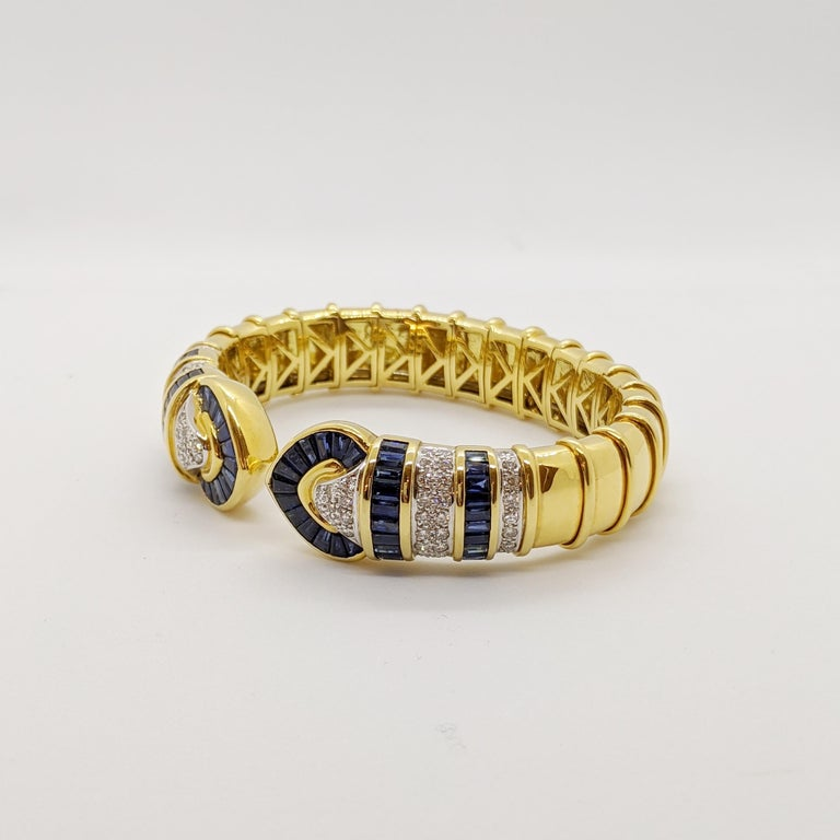 No details were spared in this beautiful 18 karat yellow gold cuff bracelet. Long tapered blue sapphires and pave round brilliant diamonds are set forming two hearts. The design continues with rows of baguette sapphires and pave diamonds. Ribbed