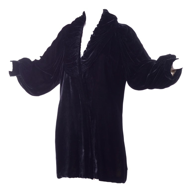 This is a gorgeous Edwardian vintage black velvet evening coat with a gathered puffy collar and puff sleeves. The coat is beautifully lined in pale pink silk satin. This coat has a tie on the inside that closes one side but no closure for the other.