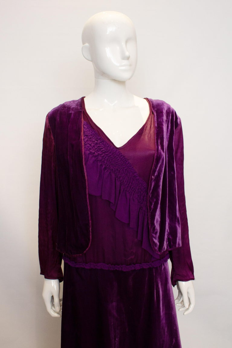 A stunning purple gown from the 1920s. The dress has a v neckline and silk gathering at the front. It has satin sleaves and frill detail at the back.