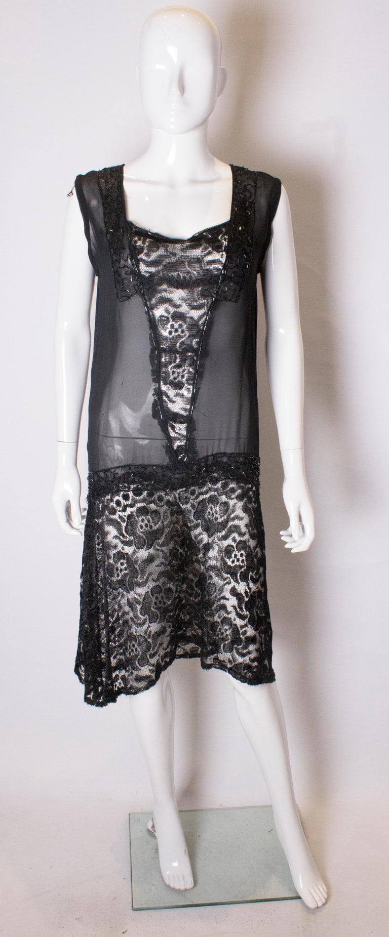 A pretty 1920s style cocktail dress. The dress has a v neckline with a lace skirt  , central lace panel and bead decoration.
