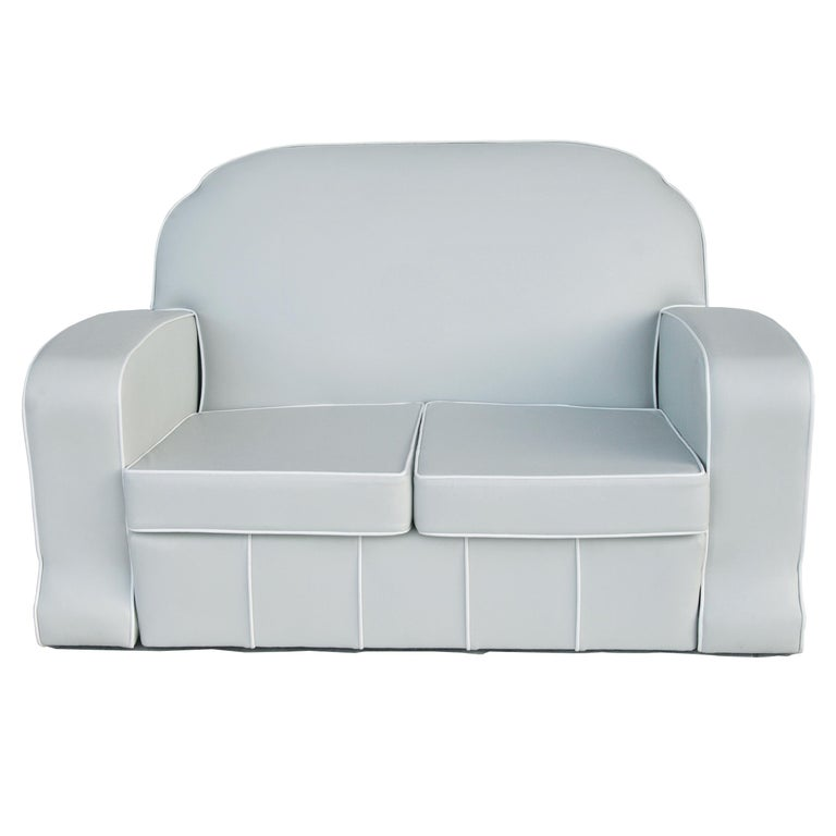 Newly upholstered in off-white/light grey vinyl with an accentuated white piping and