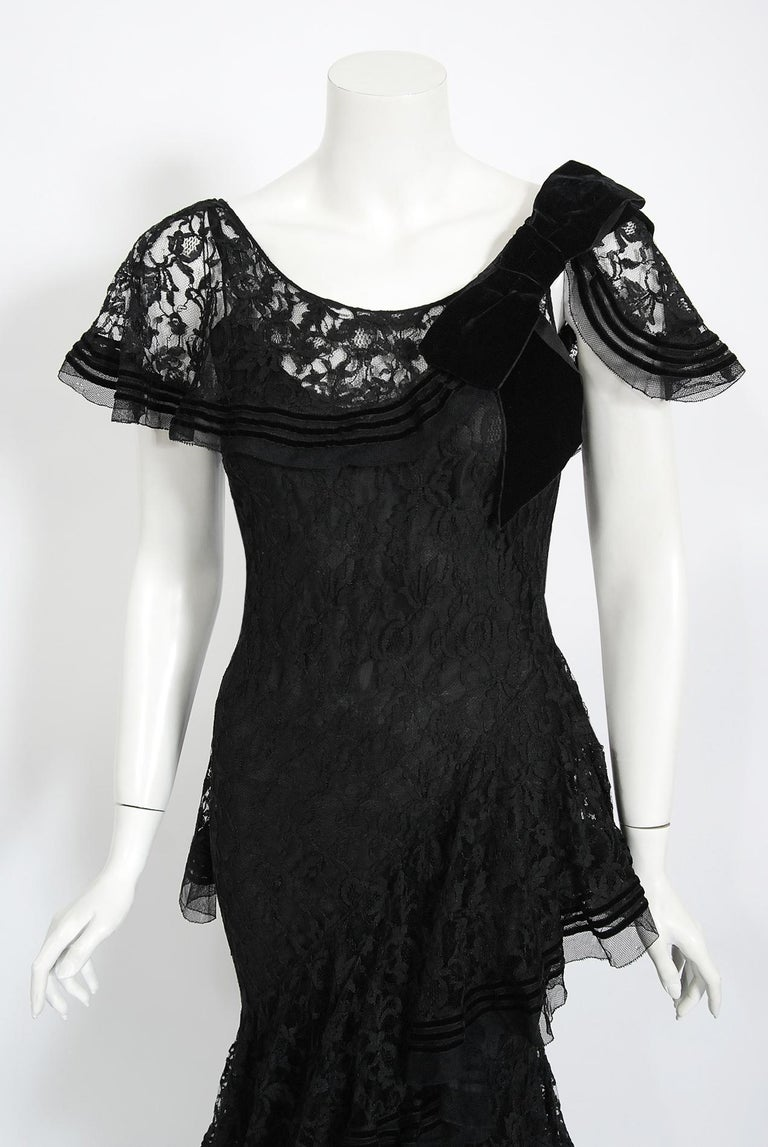 Undiminished by time, this mid 1930's black lace couture gown still casts its magical spell. This exceptional French beauty is fashioned in the highest quality black floral patterned lace that has been carefully embellished with velvet striped