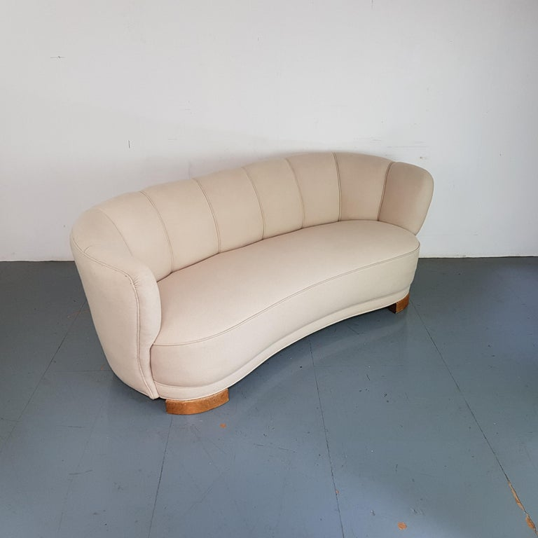 Danish curved Banana sofa upholstered in its original cream / off white fabric, with wooden legs.