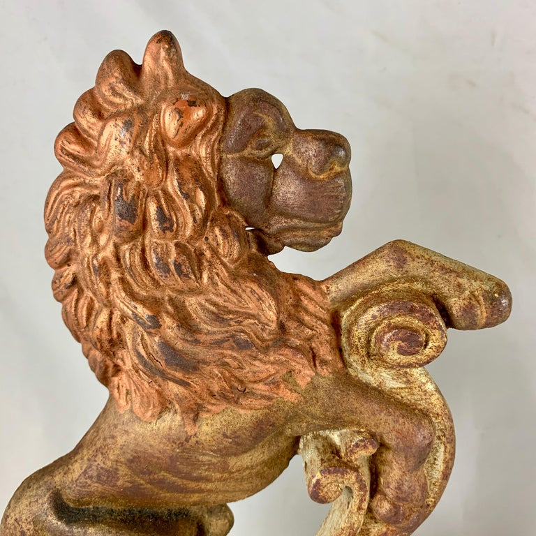 A pair of French painted cast iron doorstops or bookends in the form of heraldic lions, circa 1930s and retaining the original painted and gilded finish.  The lion is a common image used in heraldry. It traditionally symbolizes courage, nobility,