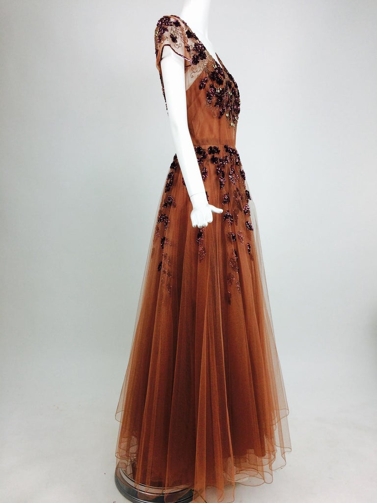 Vintage 1940s beaded and sequined tulle evening gown. This beautiful dress was made in England, rare because it's from the 1940s when war rationing made dressmaking almost non existent. It is the most amazing cinnamon colour tulle. Plum sequins,with