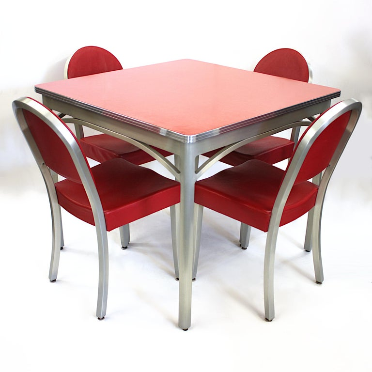 Vintage 1940s cafe table and chairs set by GoodForm Furniture Co., a division of The Gernal Fireproofing Co.   Set features:  - Welded, brushed-aluminum frames - Red Formica table-top - Red vinyl upholstery - 4 chairs  Dimensions:  Table: