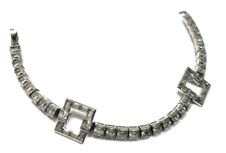 """This 1950s vintage retro bracelet features clear crystals in a rhodium silver tone setting.  In excellent condition, this bracelet measures 7"""" x 5/8"""" with a fold-over clasp."""