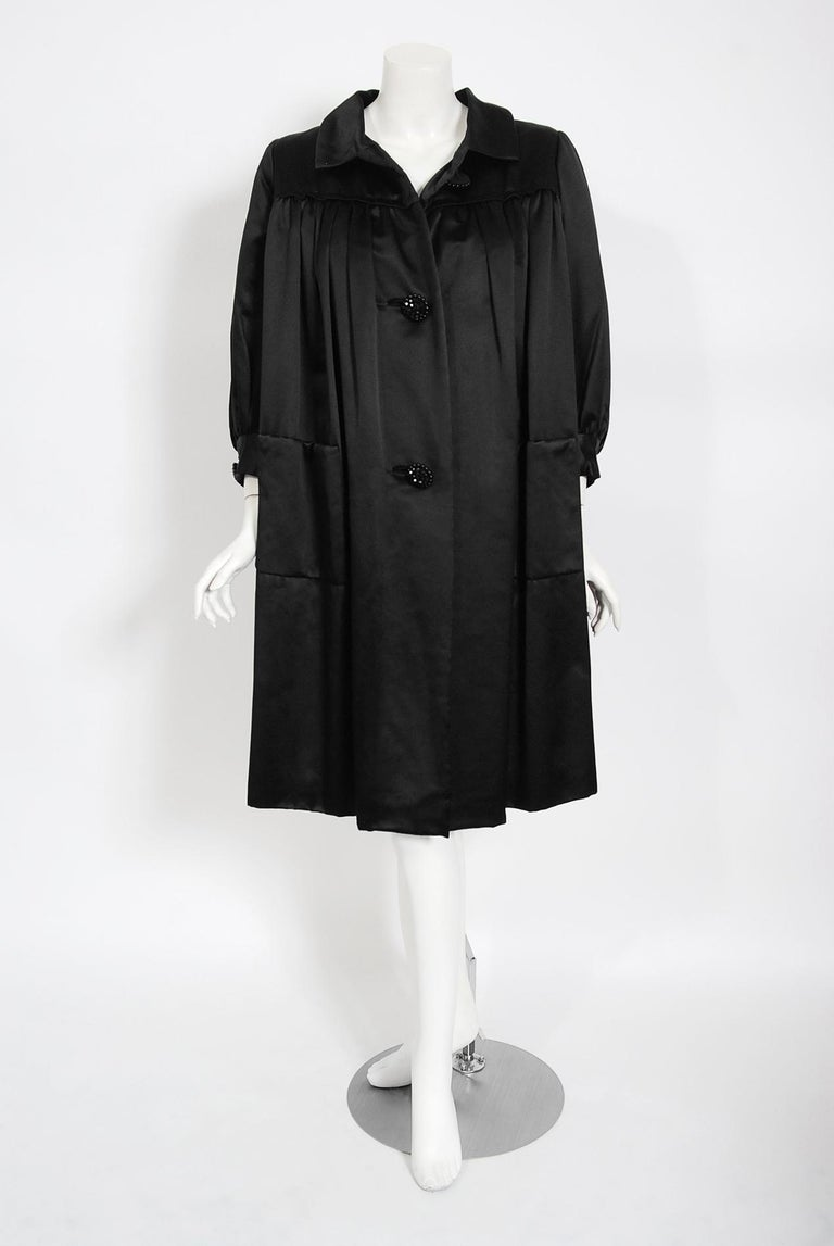 This exquisite Traina-Norell designer coat, fashioned in a high-quality duchess silk satin, exemplifies their signature blend of couture-level quality with quintessentially American style—elegant in its simplicity. This was a difficult piece to