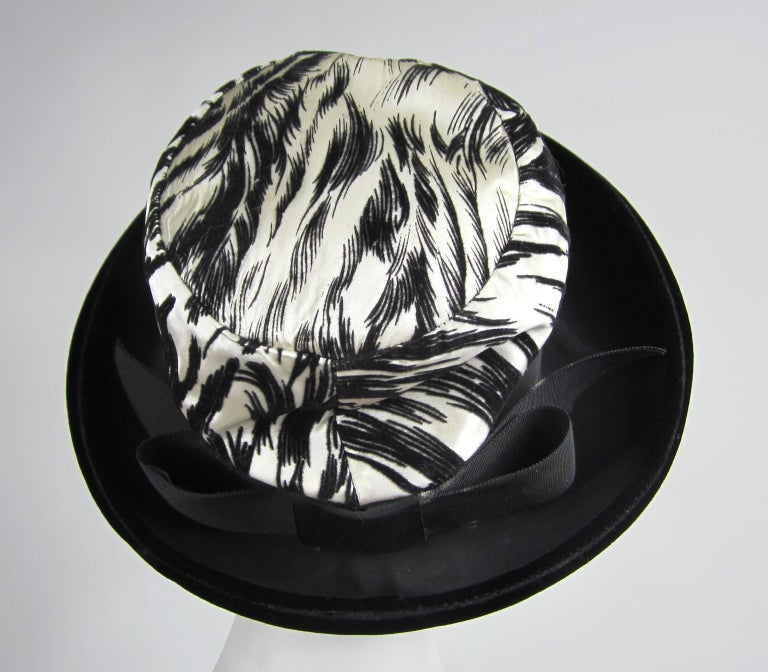 1960s Chesterfield Original Black and White Velvet Brimmed hat. Rolled brim. Large Bow at the back. Hat is approx 6-3/4 Small. Brim is 3.75 inches, sits up approx 6 inches.  Please check our storefront for hundreds of items including New, Never worn