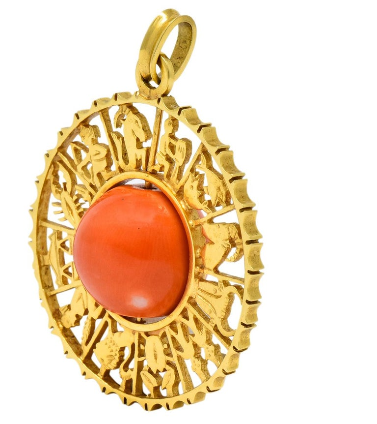 Featuring a round rotating coral bead measuring approximately 12.8 mm, opaque pinkish-orange in color with white and dark pinkish-orange areas  Surrounded by pierced zodiac calendar with each section featuring a motif of  a zodiac sign  Completed by
