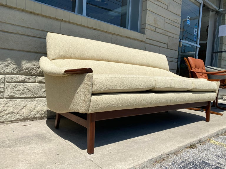 This wonderfully unique sofa was created by R. Huber & Co., and is in overall good condition. Walnut wood details. Cream colored nubby bouclé upholstery. Wear consistent to age and use. circa 1960s. Canada. Dimensions: 30