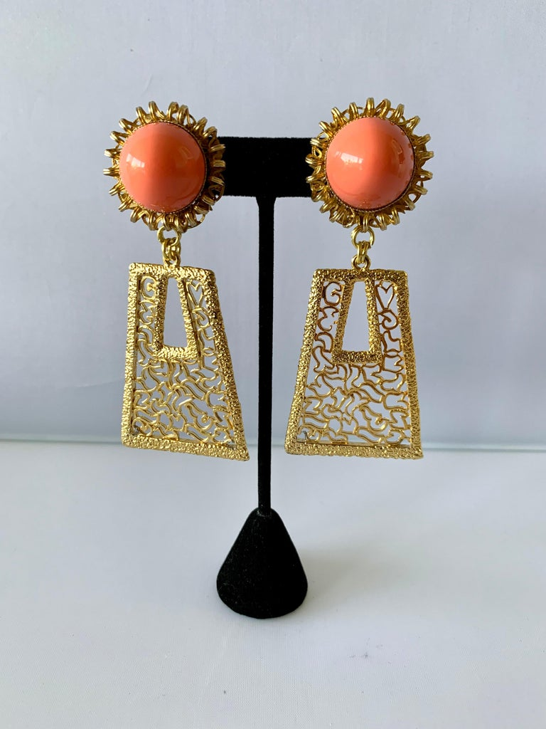 Vintage oversized 1960's geometric statement clip-on earrings comprised out of gold-tone metal adorned by large faux coral sugarloaf cabochons - designed by William de Lillo.