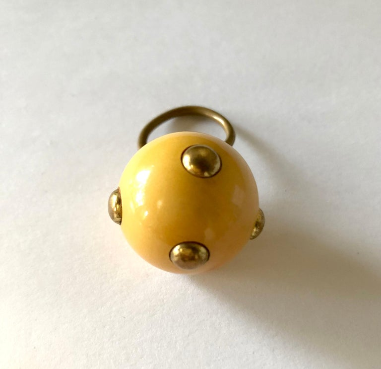 Vintage 1960's beige tone bakelite ring with brass studs made by Kenneth Jay Lane, New York.  Ring is currently a finger size 6.75, is slightly adjustable and a bit out of round. Ball is 1