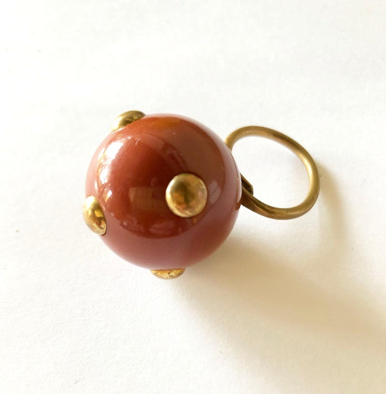 Vintage 1960's mauve bakelite ring with brass studs made by Kenneth Jay Lane, New York.  Ring is currently a finger size 6.5 and is slightly adjustable and a bit out of round. Ball is 1