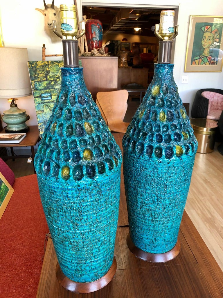 Lamps are in overall good condition. Glazed. Varied hues of blue and splash of yellow-green. Hand-crafted texture. Walnut base. Unknown artist or maker, circa 1960s. Dimensions: 27