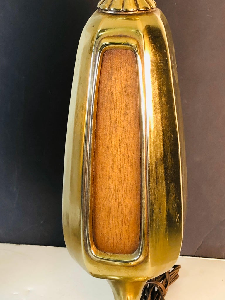 """Vintage 1960s brass and wood accented table lamps by Laural Lamp Co. These lamps are wired for the US and in working condition. The lamps are double sided and have a square floral base. Socket, 37""""H. Harp, 4.25"""" diameter x 9"""" height. Shades are"""