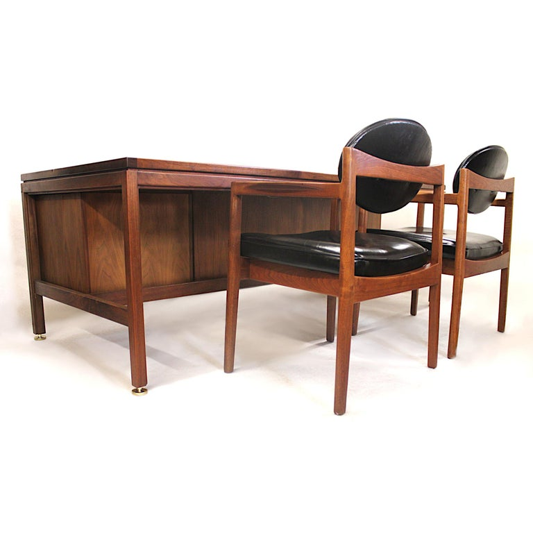 This wonderful office set by Jens Risom includes an imposing yet inviting executive desk and two matching guest chairs. The desk is in excellent original condition and includes many interesting details including; dual locking cabinets, solid brass