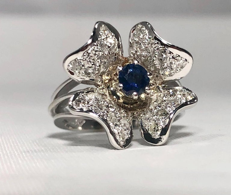 Vintage 1970's 14 karat Sapphire and diamond flower cocktail ring. This is a vintage creation approx. Circa 1970. This piece is created in 14 karat white gold and weighs 6.5 grams, 4.2 dwt.. A full cut round 0.36 carat  Sapphire is the center stone