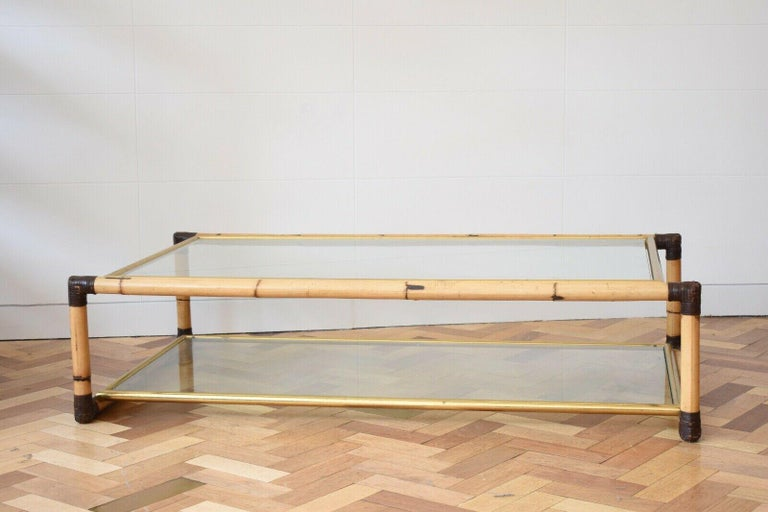 This lovely 1970s coffee table is the creation of Italian designer Alberto Smania. It features two glass tops which sit on thin brass frames, encased in bamboo with leather detailing on its corners. The rectangular table is both practical and