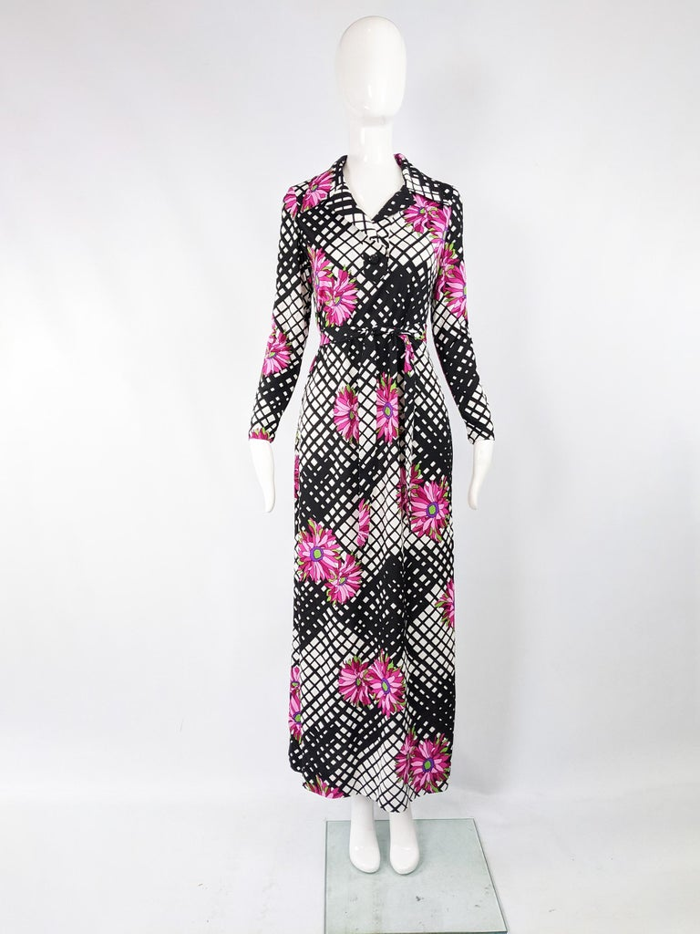"""A beautiful vintage maxi dress from the 70s in a black and white synthetic jersey with a bold pink floral print. It has long sleeves and a wide collar.   Size: Unlabelled; fits like a UK 12/ US 8/ EU 40. Please check measurements.  Bust - 36"""" /"""